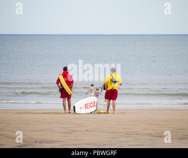 Lifeguards on Seaton Carew beach watching children and adult paddle in the sea. UK - Stock Photo
