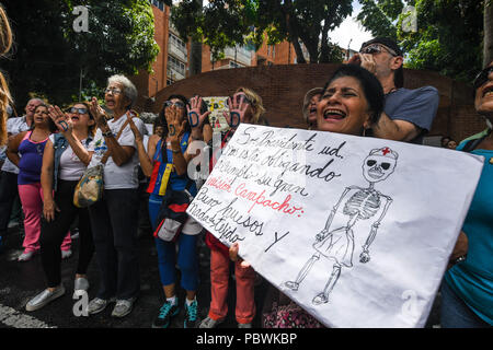Caracas, Miranda, Venezuela. 30th July, 2018. Health workers seen protesting with a banner.Nurses, doctors and patients protest in front of the World Health Organization offices in Caracas for the lack of medicines and treatment in the hospitals. The government led by President Nicolas Maduro still does not solve the problem in the health sector and does not allow the humanitarian aid of other nations. Credit: Roman Camacho/SOPA Images/ZUMA Wire/Alamy Live News - Stock Photo