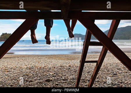 Happy kids have fun on beach walk. Children sit on lifeguard tower edge, dangling bare feet, look at sea surf. Black silhouette. Vacations travel life - Stock Photo