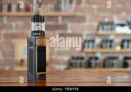 Electronic cigarette with ejuice bottle on a background of vape shop. E-cigarette for vaping. Popular vape devices - Stock Photo