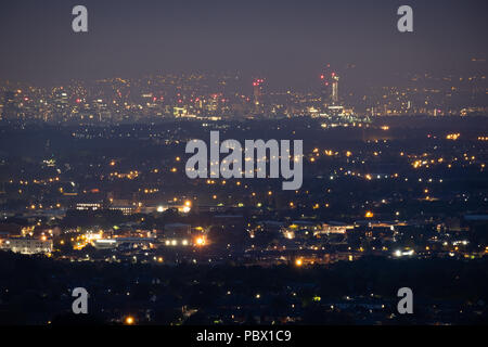 Night view of the city of Manchester,UK set out below and at a distance with a wide view of the lights taken from Winter Hill, Bolton - Stock Photo