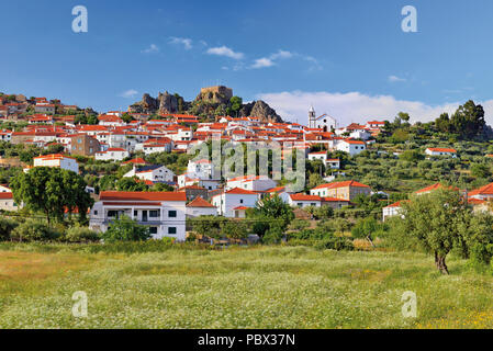 View to a charming small village with a castle ruin on the top - Stock Photo