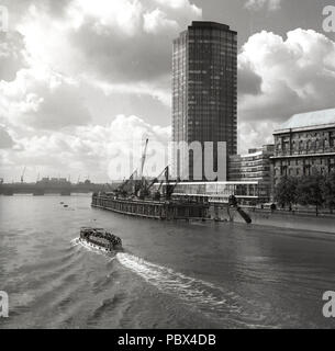 1960s, historical, a pleasure boat goes down the river Thames at the cleveland bridge landing stage or floating platform, beside a newly built modern high-rise office building  London, England, UK. The 60s saw the riverside of the Thames change for ever as wharves were developed into tower blocks and housing. - Stock Photo