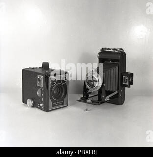 1950s, historical, picture shows two of the most popular amateur film cameras of the era, a Kodak 'Brownie' box camera and a folding medium format camera. - Stock Photo