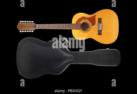 Musical instrument - Vintage twelve-string acoustic guitar hard case isolated on a black background. Stock Photo