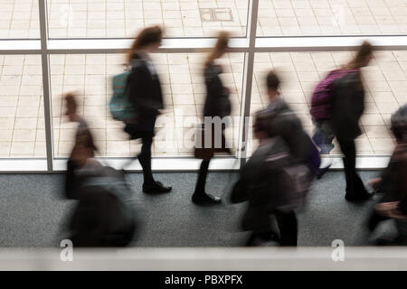 Secondary school pupils moving by a window in a school UK, blurred movement - Stock Photo
