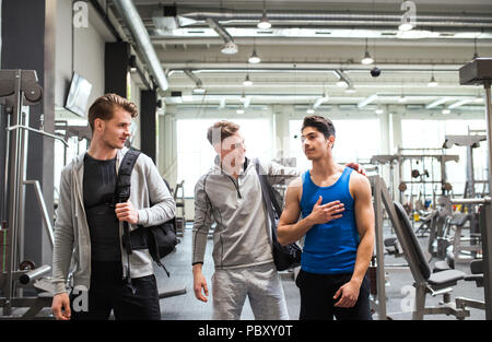 Young friends in modern crossfit gym, greeting each other. - Stock Photo