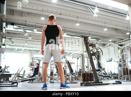Young man in modern crossfit gym, standing. Rear view. - Stock Photo