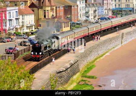 The English Riviera Express running alongside the sea wall at Dawlish, heading for Kingswear. - Stock Photo