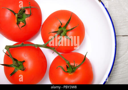ripe red vine grown organic tomatoes in white metal bowl - Stock Photo