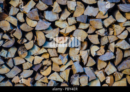 A pile of chopped logs ready to use as fuel in a wood burning stove. - Stock Photo