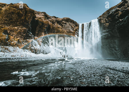 Skogafoss waterfall in Iceland with rainbow on a sunny day with blue sky. - Stock Photo