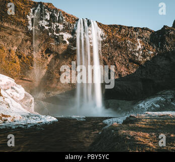 Wonderful landscape from Seljalandsfoss Waterfall in Iceland on a clear day with blue sky and snow. - Stock Photo