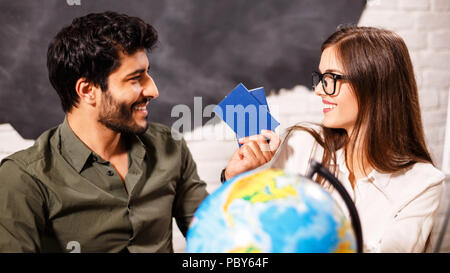 Young couple making plans for their next travel destination with the globe map and passports - Stock Photo