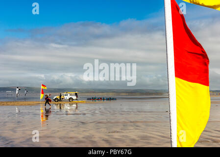 Surfers and safety marker flags on the beach at Westward Ho!, Devon, UK - Stock Photo