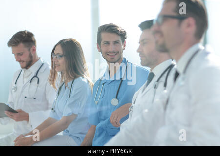 Close up of smiling doctor sitting with his team - Stock Photo