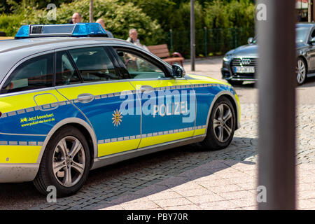 TITISEE-NEUSTADT, GERMANY - JULY 16 2018: Patrolling police officers in German village on sunny day. - Stock Photo