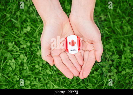 Macro closeup shot of hands palms holding round badge with red white canadian flag maple leaf on green grass forest nature background outside Canada D - Stock Photo