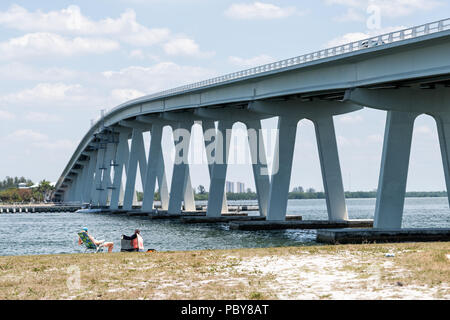 Sanibel Island, USA - April 29, 2018: People, young couple fishing, rods, in bay sitting on beach chairs during sunny day in Sanibel Island under toll - Stock Photo