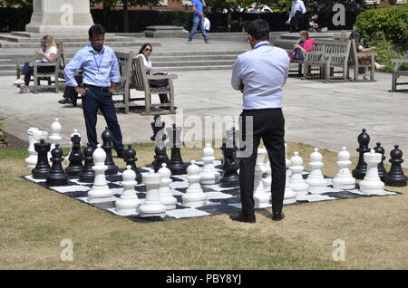 Two Asian businessmen playing outdoor chess on their lunchbreak in Grosvenor Square, Mayfair, London - Stock Photo