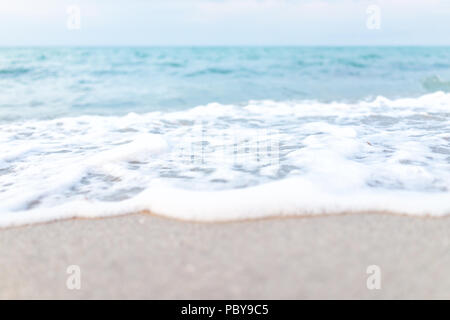 Foamy wave crashing macro closeup on shore in Sunny Isles Beach, North Miami, Florida during evening sunset with colorful water, wet sand, nobody - Stock Photo