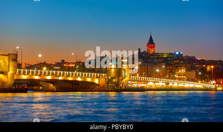 The Galata Bridge over Golden Horn bay in Istanbul at night, Turkey - Stock Photo