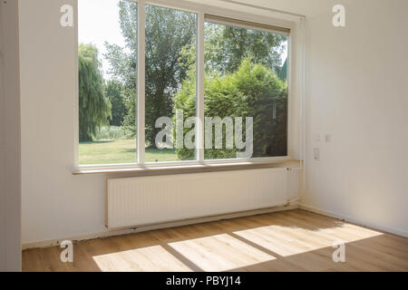 Empty white room with hardwood parquet floor, big window and walls and sunlight from window, With a beautiful green forest nature view modern house - Stock Photo