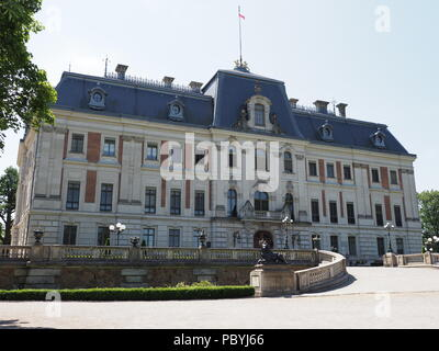 Antique neo baroque castle museum and courtyard at park of european Pszczyna city in Poland with cloudy blue sky in 2018 warm sunny spring day on June - Stock Photo