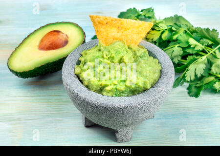 A photo of guacamole sauce in a molcajete, traditional Mexican mortar, with a nacho chip, cilantro, and avocado, on teal - Stock Photo