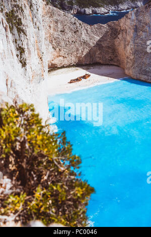 Vertical shot of shipwreck on Navagio beach with turquoise blue sea water surrounded by huge white cliffs. Famous landmark location on Zakynthos island, Greece - Stock Photo
