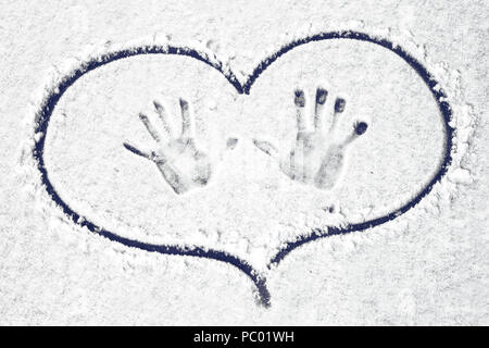 handprints on the snow circled in heart, background image - Stock Photo