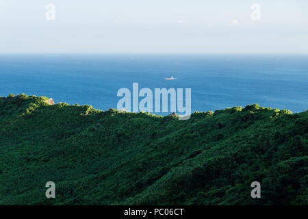 Last sun on the rim of the crater of Ilchulbong with view on ocean with boat , Seongsan, Jeju Island, South Korea - Stock Photo