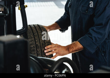 Cropped shot of a mechanic checking the condition of a automobile wheel. Man examining the wear and tear of car tire in garage. - Stock Photo