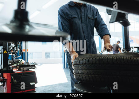 Mechanic removes car tire service station. Man working on machine for removing rubber from the wheel disc. - Stock Photo
