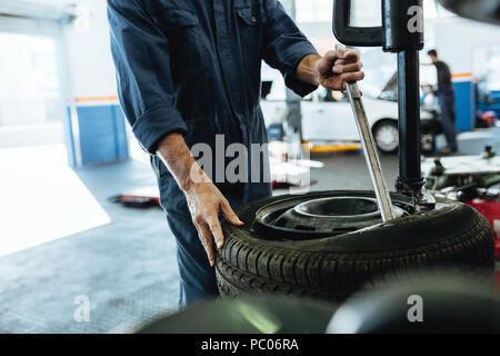Mechanic changing car tire on a tire changing machine in workshop. Cropped shot of mechanic hands removing tire from disc on machine. - Stock Photo