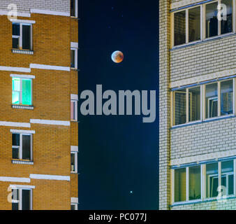 Moon eclipse in full moon. Super blue blood moon in July 27, 2018, Belarus. Cityscape: facade of a multi-storey building against the background of the - Stock Photo