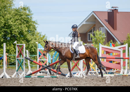 Girl riding horse for warm up before perfomance - Stock Photo