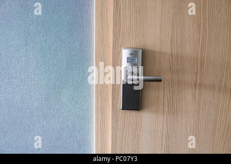 Hotel electronic lock on wooden door and with a blue wall - Stock Photo