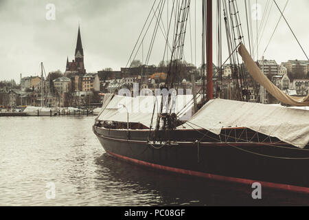 Sailing ship moored in old port of Flensburg, Germany. Vintage stylized photo with tonal filter effect - Stock Photo