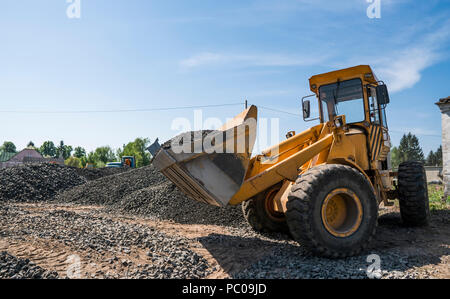 Yellow loader moving with uploaded bucket to the truck with stone gravel during road construction works. The stones for the road. Unloading stone - Stock Photo