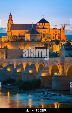 Cordoba Spain, view at night across the Roman bridge on the Rio Guadalquivir towards the Mezquita cathedral-mosque in historic Cordoba, Spain.