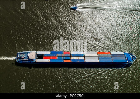 Rhine - Netherlands, July 14, 2018: aerial view of a merchant ship with a container crossing the river Rhine in a region of the Netherlands