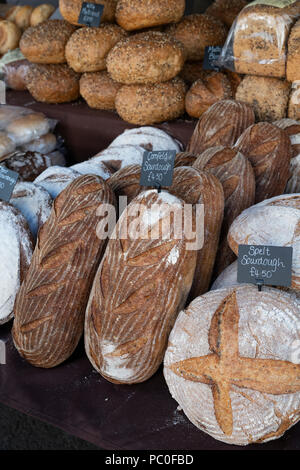 Sourdough bread for sale on a stall at a farmers market. Deddington, Oxfordshire, England - Stock Photo
