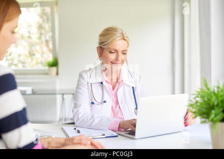 Shot of female doctor using laptop while discussing with her patient in the hospital. - Stock Photo