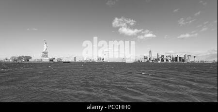 Panorama View of Statue of Liberty at New York City with Manhattan Skyline over Hudson River - USA - Stock Photo