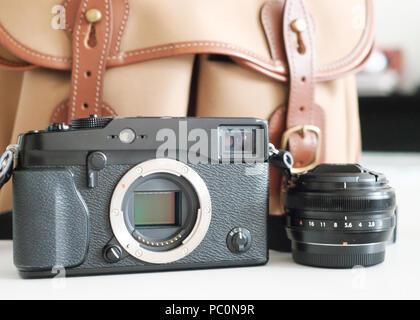 Fuji Mirrorless system camera with sensor visible, with lens and billingham camera bag - Stock Photo