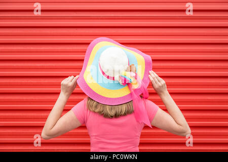 Rear view of fashionable woman wearing colorful sunhat against red background - Stock Photo