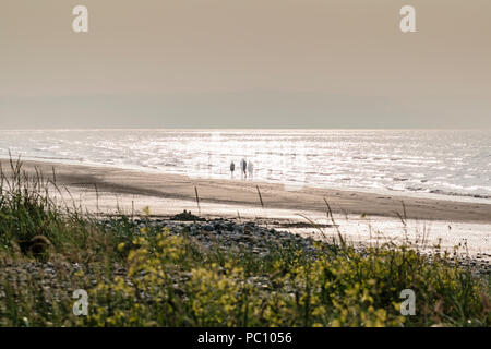 Walkers strolling on the beach at Red Wharf Bay on Anglesey near Llanddona North Wales uk - Stock Photo