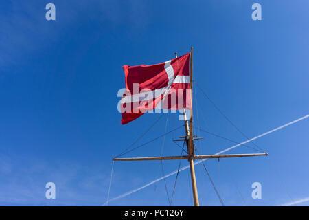 Denmark flag on a ship mast waivng against a clear blue sky - Stock Photo