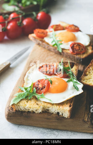Breakfast sandwich with egg, cheese and tomato on rustic wood cutting board. Closeup view, selective focus. Toned image - Stock Photo